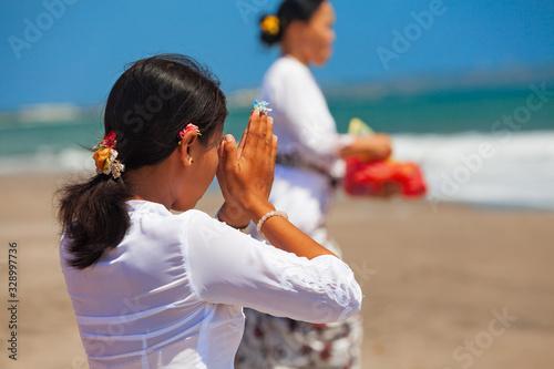 Photo Young balinese women praying with namaste hands on sea beach