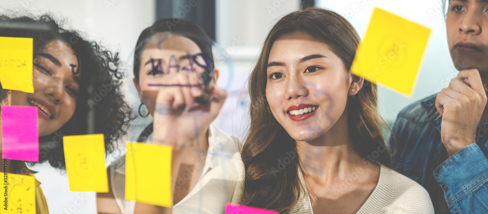 Fototapeta Banner of asian creative woman smiling and meeting at office use post it notes to share idea and planning project. Group of employee brainstorming idea on glass wall and sticky. Brainstorming concept.