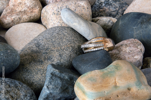 Fotografie, Tablou Golden ring with a lot of zirconium stones lying on a coastal pebble