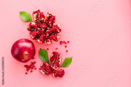 Ripe pomegranate fruit near leaf on pink background top-down copy space