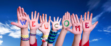 Many Children Hands Building Colorful Word Welcome. Blue Sky As Background