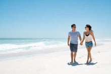 Young Happy Couple Walking On Beach