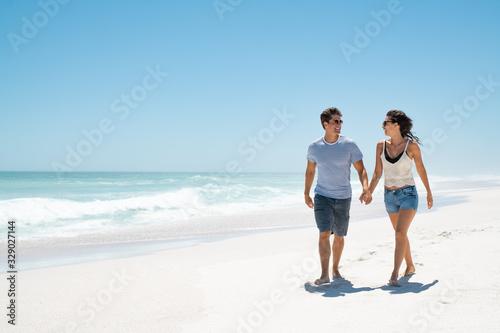 Obraz Young happy couple walking on beach - fototapety do salonu