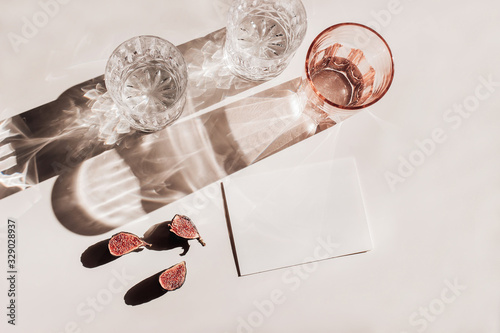Summer stationery still life scene. Glasses of water, cut figs fruit. Pink table background in sunlight. Blank business, greeting card, invitation mockup scene. Long harsh shadows. Flat lay, top view