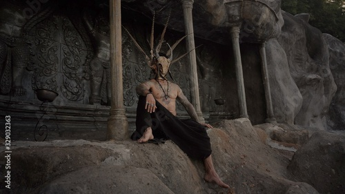 Fotografia Tattooed masked skull ethnic pagan shaman sit on stage an ancient temple