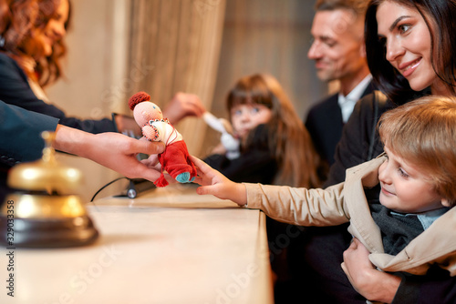 Fototapety, obrazy: Where you always feel at home. Happy family checking in hotel at reception desk. Hotel worker is giving a toy for a boy while welcoming guests at the hotel