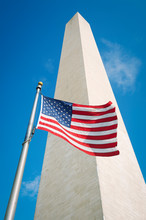 American Flag Flying Outdoors In Bright Sun At The Foot Of The Washington Monument In Washington, DC, USA