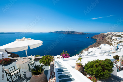 Fototapeta Sweeping panoramic view of the Santorini caldera with Mediterranean blue waters at the foot of classic Greek whitewashed cliffs obraz