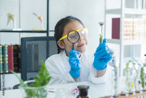 little asian girl elementary school looking into magnifying glass at the flower on desk at school.scientist making experiments in home laboratory. child and science. education concept. .