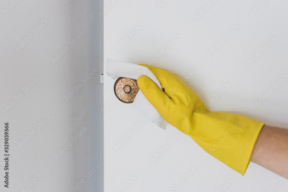 Fototapeta disinfecting surfaces from bacteria or viruses sill-life, hand with glove cleaning door knob with disinfectant wet wipe