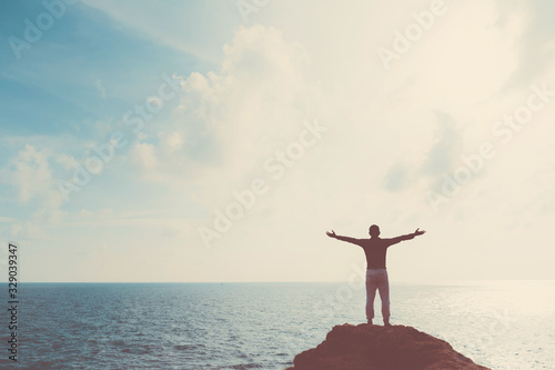 Copy space of man raise hand up on blue sky at beach and island background.