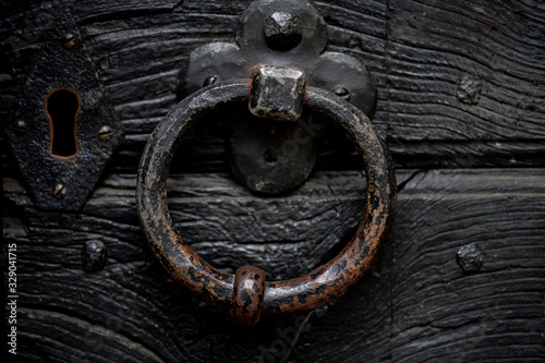 massiver Türklopfer aus Eisen an einer schweren schwarzen Holztür Wallpaper Mural