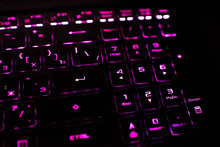 Computer Keyboard With Russian And English Layout. Backlit By Neon Light.
