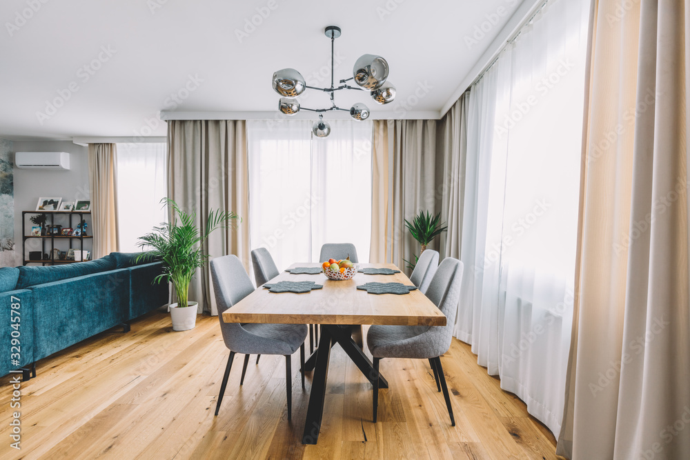 Fototapeta Dining room with wooden table and floor in modern apartment.