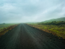 Gravel Road Leading Into A Misty Valley, Rocky Mossy Green Landscape Volanic Dirt Track