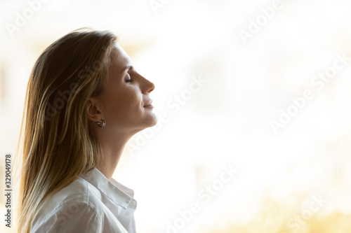 Side view close up head shot young mindful businesswoman breathing fresh air, managing stress at office Canvas Print