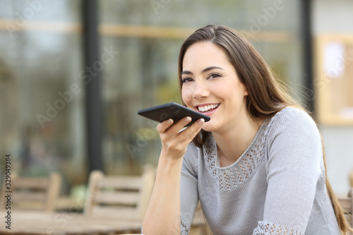 Fotografia Happy woman using voice recognition on her phone