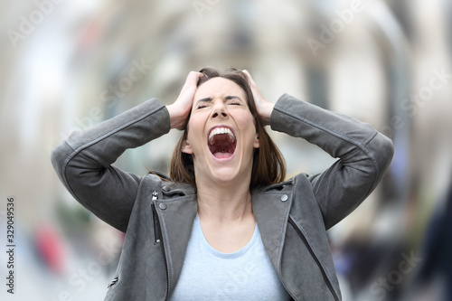 Stressed woman suffering anxiety attack on city street Canvas