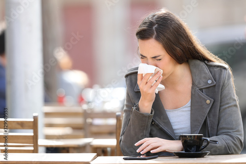 Fototapeta Woman blowing her nose with tissue on a coffee shop obraz