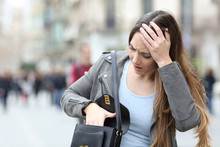 Worried Woman Looking Inside Her Bag On Street
