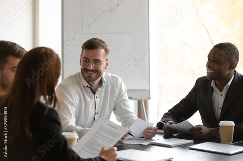 Fototapety, obrazy: Happy mixed race confident business partners meeting corporate clients, discussing common project ideas. Group of smiling diverse female male employees working together, doing paperwork at workplace.