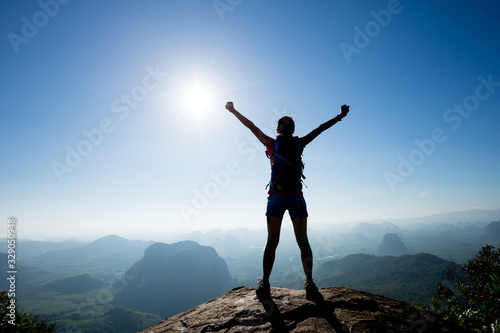 Photo Cheering woman backpacker enjoy the view on sunrise mountain top cliff edge