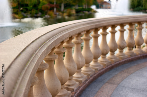 Photo Close up stone railings in front of a pond with fountains