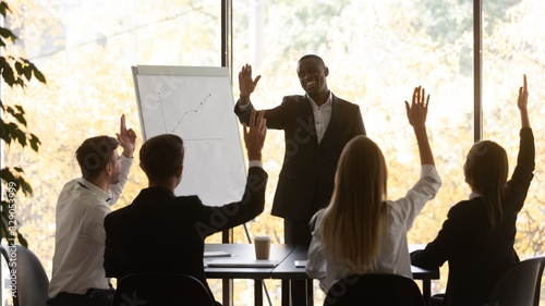 Obraz Engaged young business team raising hands, taking part in voting, making unanimous decision at brainstorming meeting in office. Motivated group supporting new project of african american leader. - fototapety do salonu