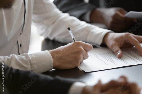 Fototapeta Close up young male employee manager customer hands signing paper contract after checking. Millennial investor client put signature at business agreement between partners. Editor making corrections. obraz