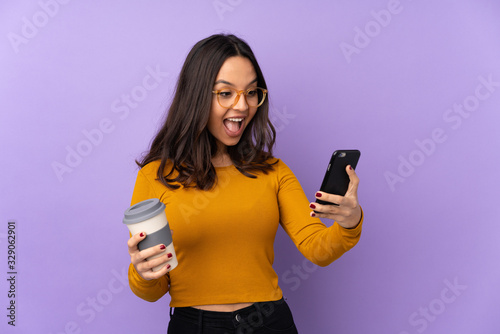 Fototapeta Young mixed race woman isolated on purple background holding coffee to take away and a mobile obraz