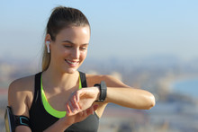 Happy Runner With Earbuds Checking Smart Watch