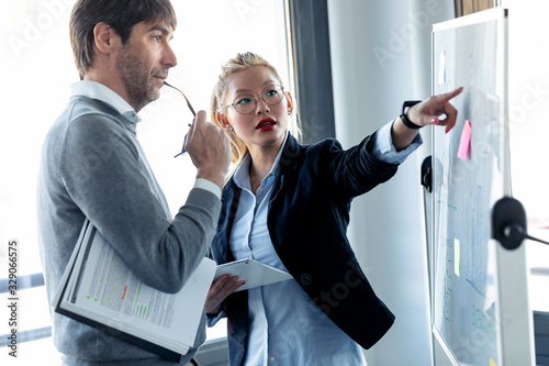 Foto Elegant young businesswoman pointing at whiteboard and explaining to the project to her colleague on coworking place