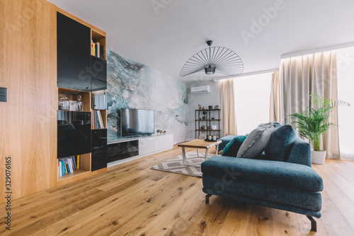 Obraz Open space living room with a big couch in a modern apartment. - fototapety do salonu