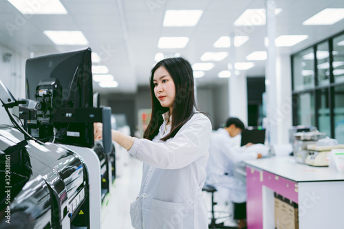Photo young female scientist working with automation blood analyzer in medical laborat