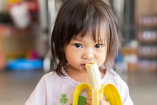 Portrait Image Of Baby 1-2 Years Old. Happy Asian Child Girl Enjoy Eating And Biting A Banana With Sweet Smiling. Food And Healthy Kids Concept.