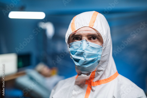 Obraz Man with protective suit and face mask indoors, coronavirus concept. - fototapety do salonu