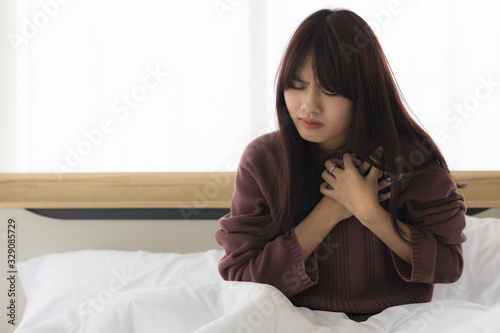 Photo Asian woman in her bedroom uses her hand to hold her heart due to the aggravated heart disease