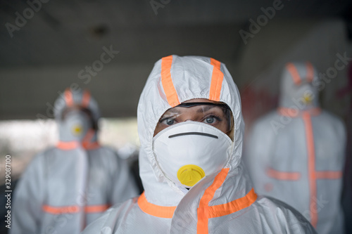 obraz PCV People with protective suits and respirators outdoors, coronavirus concept.