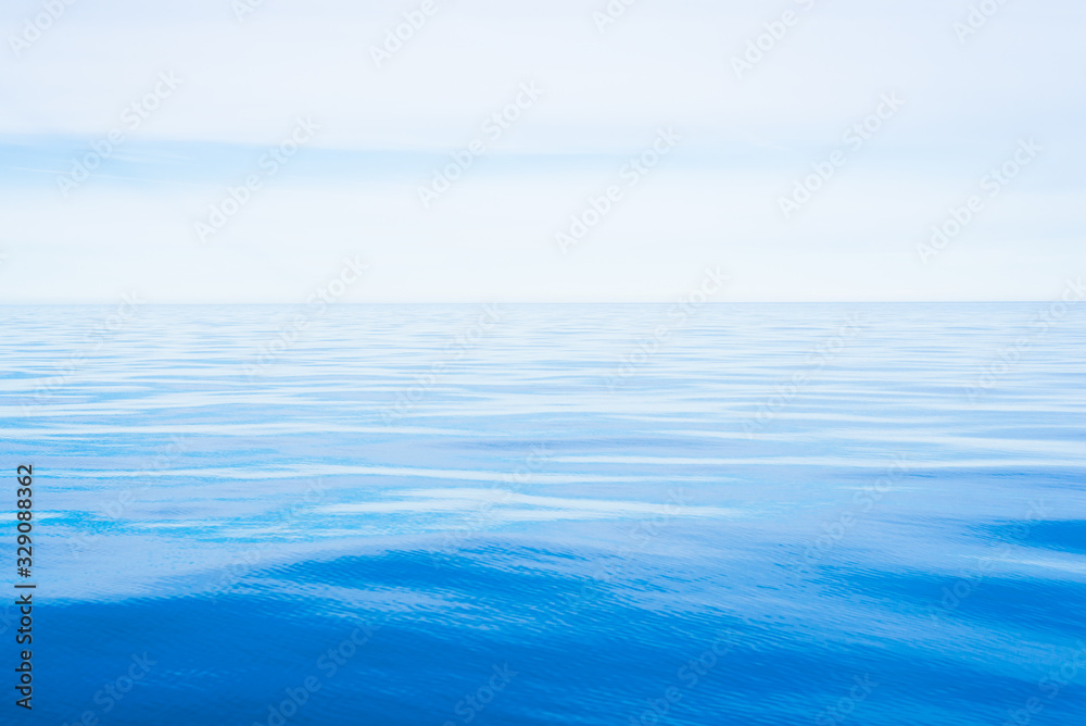 Fototapeta Sea water texture. Clear blue sky with white clouds. Reflections on water. A view from the sailboat. Baltic sea, Estonia