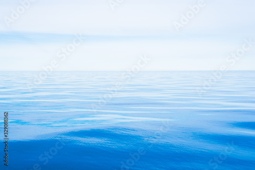 Fototapeta Sea water texture. Clear blue sky with white clouds. Reflections on water. A view from the sailboat. Baltic sea, Estonia obraz