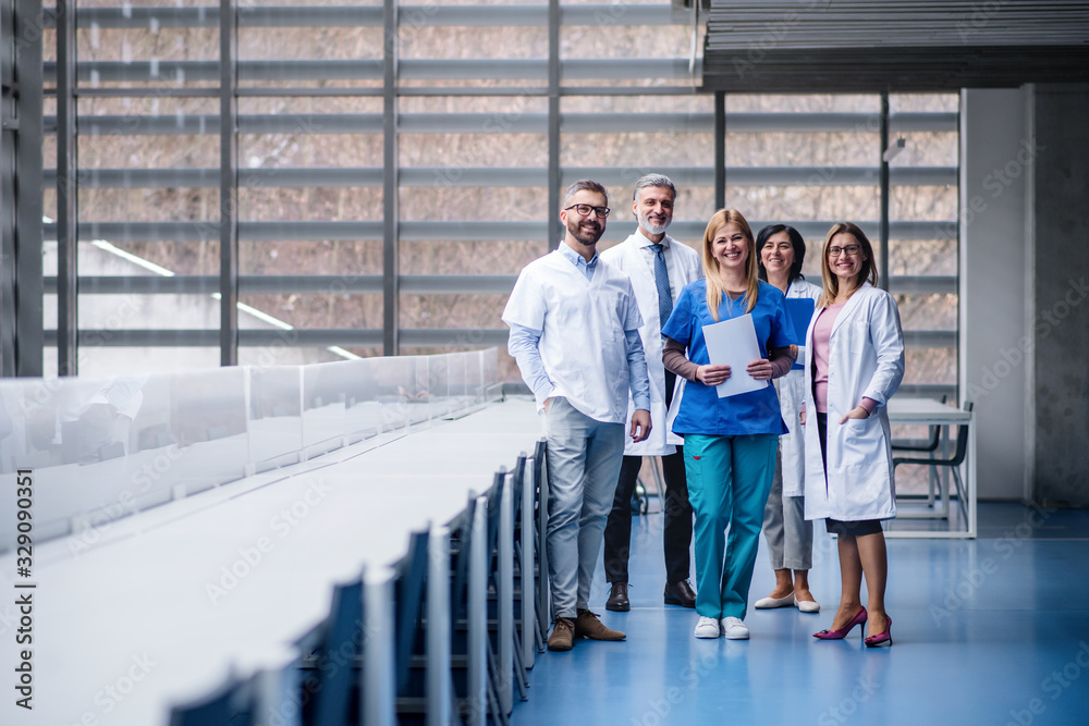 Fototapeta Group of doctors standing in corridor on medical conference.