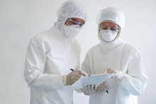 Doctor And Nurse Wearing PPE And Looking For Corona/covid-19 Virus Infected Patient's Laboratory Report