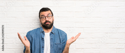 Handsome man with beard over white brick wall making doubts gesture Canvas-taulu