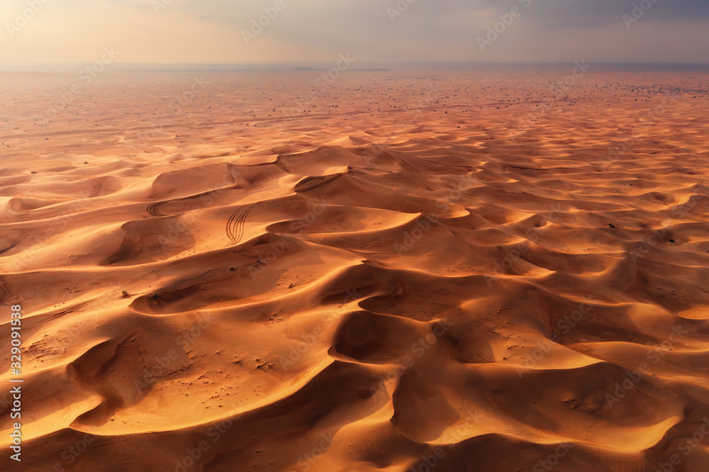 Fototapeta Aerial view of red Desert Safari with sand dune in Dubai City, United Arab Emirates or UAE. Natural landscape background at sunset time. Famous tourist attraction. Pattern texture of sand. Top view.
