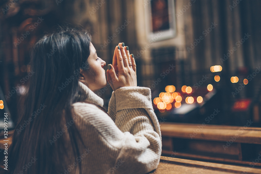 Fototapeta a young pretty woman came to the temple to pray to God. The parishioner of the church sits on a bench with her hands folded for prayer and heartily prays. copy space