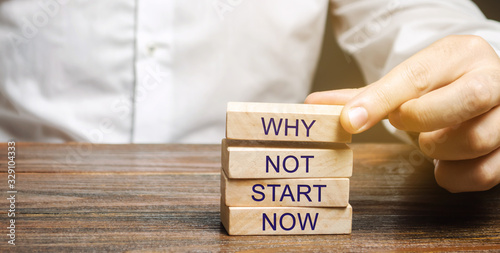 Fotografia Businessman puts wooden blocks with the words Why not start now