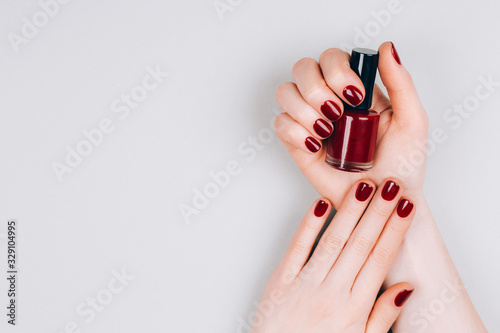 Photo Beautiful dark red manicure with a bottle of nail polish in hands on a grey background