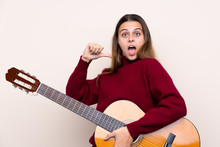 Teenager Girl With Guitar Over Isolated Background With Surprise Facial Expression
