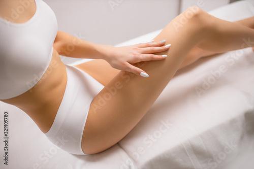 Fotografía cropped smoothy legs of slim female, woman after laser epilation in beauty salon