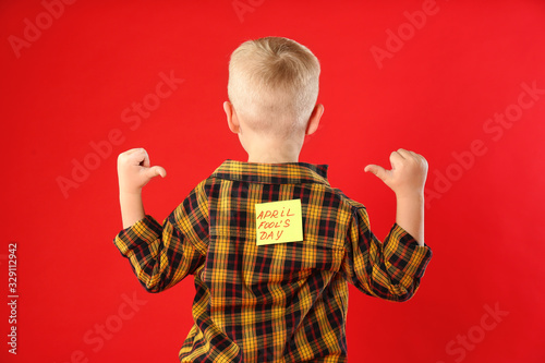 Little boy with APRIL FOOL'S DAY sticker on back against red background